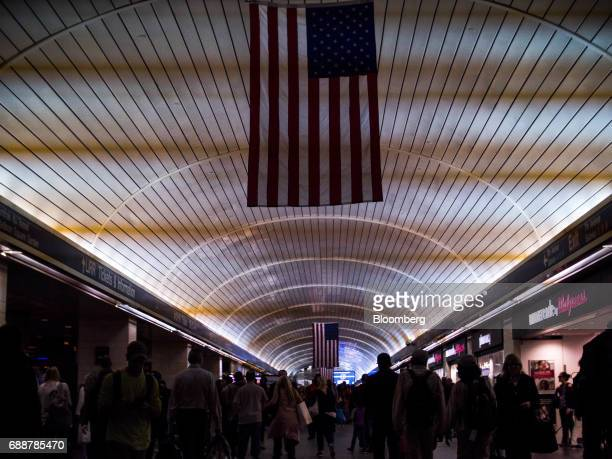 American flags hang above commuters walking through the Long Island Railroad Co concourse inside Pennsylvania Station in New York US on Friday May 26...