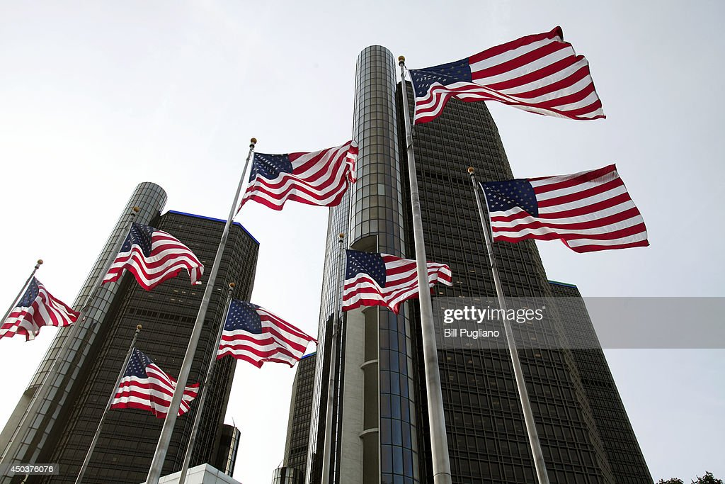 American flags wave outside the General Motors world headquarters building as the annual shareholders meeting takes place June 10 2014 in Detroit...