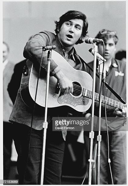 American folk singer and musician Phil Ochs performs on stage at a peace march probably at the Naumburg Bandshell in Central Park New York New York...