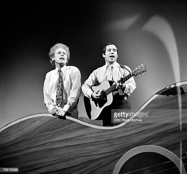 American folkpop musicians Art Garfunkel and Paul Simon of the duo Simon and Garfunkel sing and play guitar as they perform on the CBS variety...