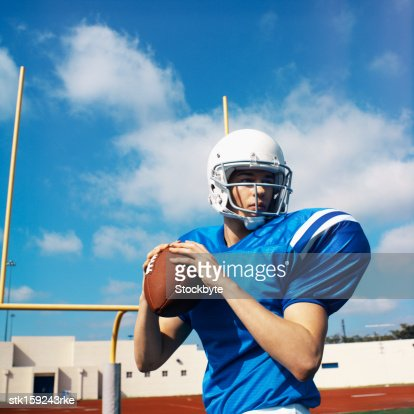 American football player (16-20) about to throw football : Stock Photo