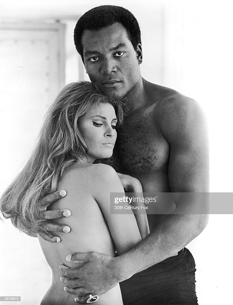 American football player and actor Jim Brown embraces actor Raquel Welch, both shirtless, in a promotional still for the film, '100 Guns,' directed by Tom Gries, 1969.