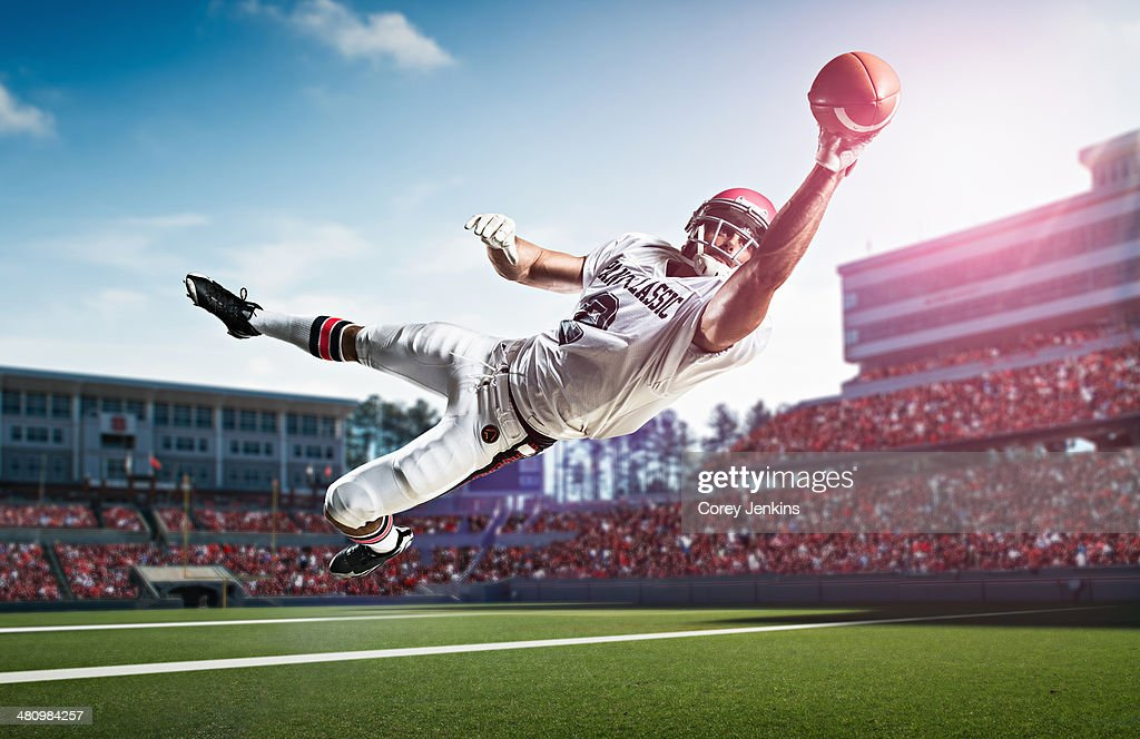 American Football Player Catching Ball Mid Air In Stadium ...