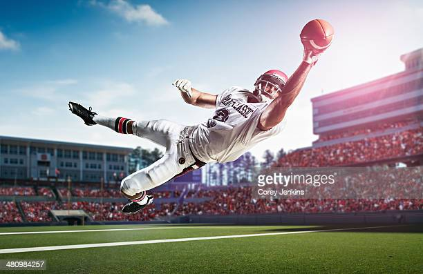American football player catching ball mid air in stadium