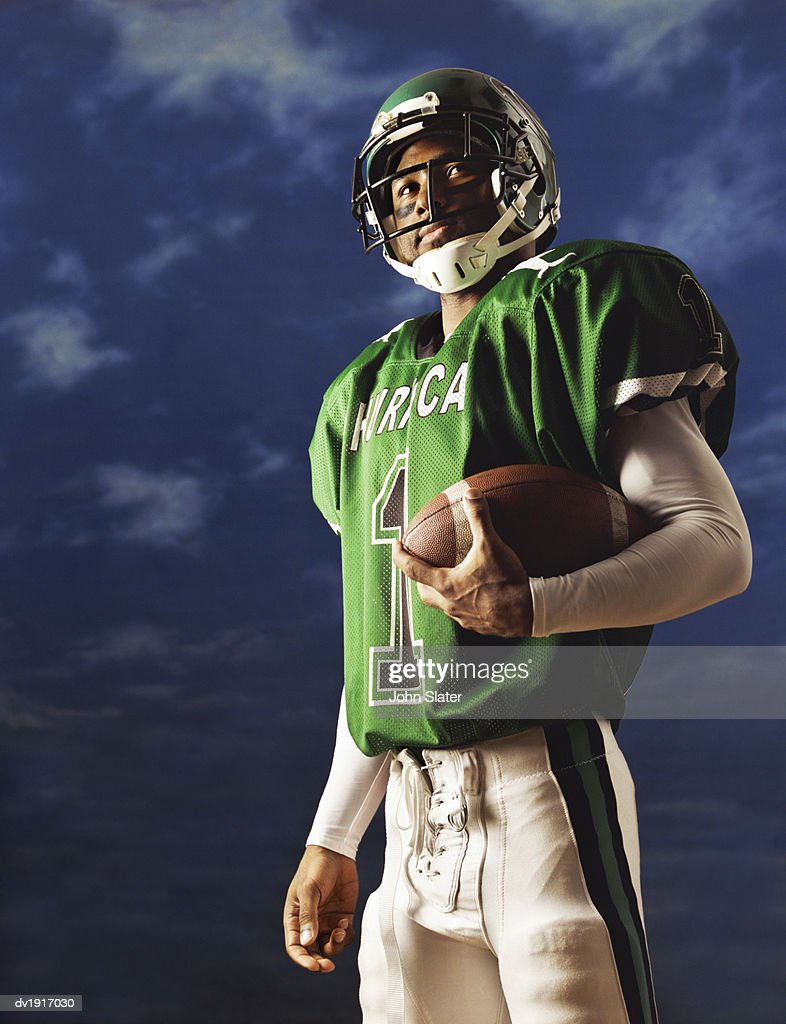 American Football Player Holding a Ball : Stock Photo