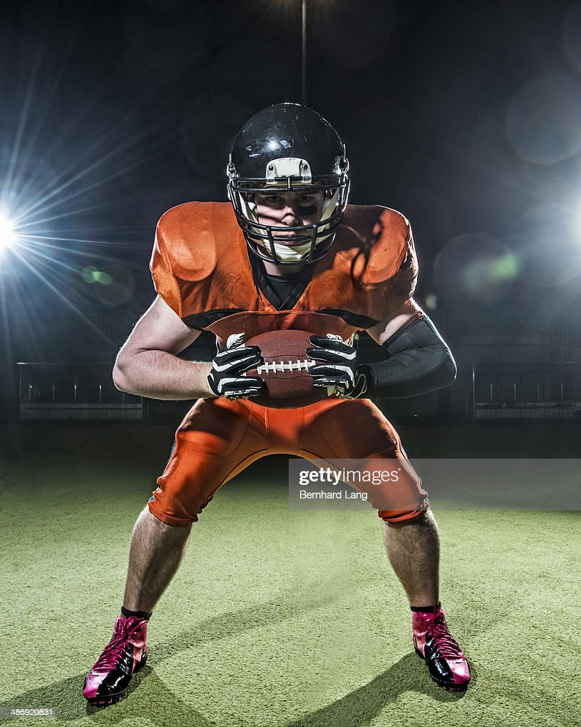 American Football Player holding ball out