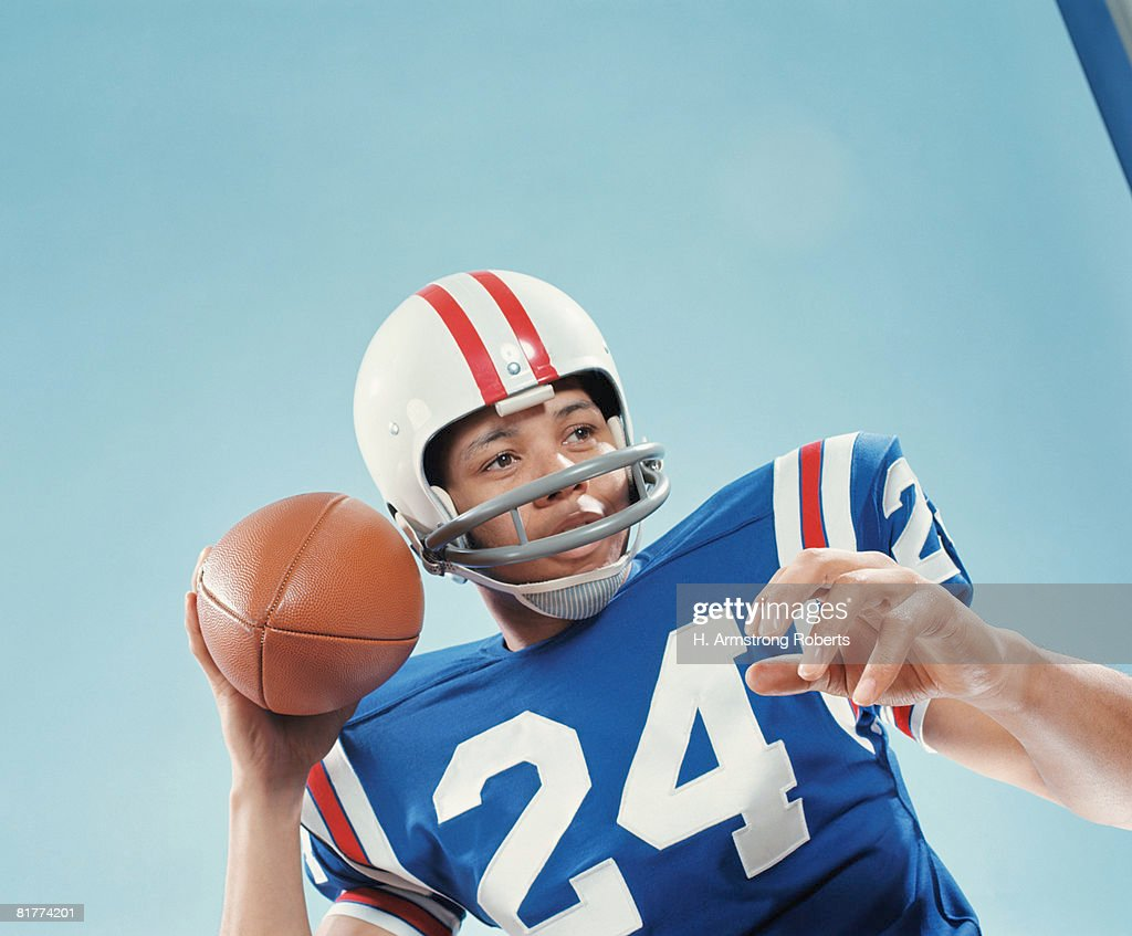 American football player holding up ball. (Photo by H. Armstrong Roberts/Retrofile/Getty Images) : Stock Photo