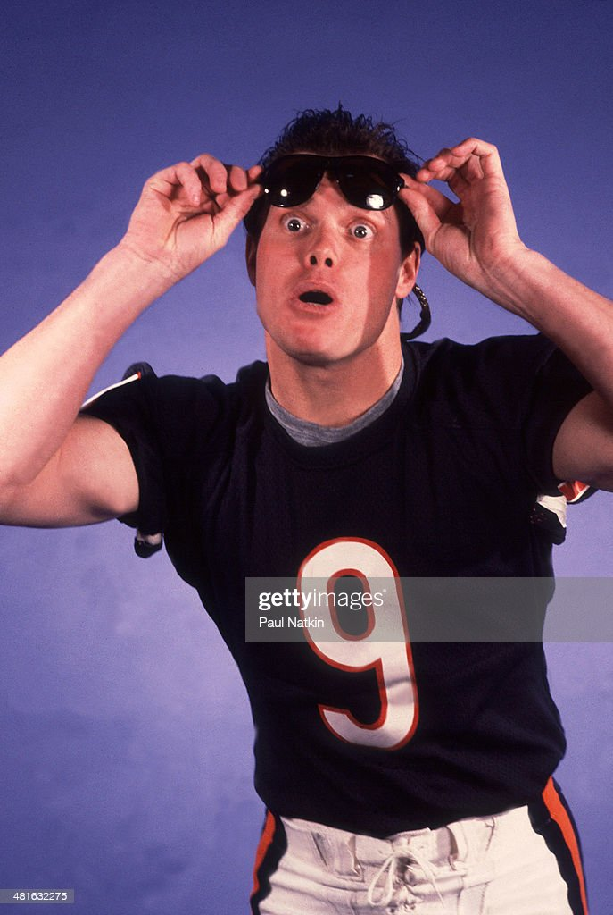 American football player <a gi-track='captionPersonalityLinkClicked' href=/galleries/search?phrase=Jim+McMahon+-+American+Football+Player&family=editorial&specificpeople=228299 ng-click='$event.stopPropagation()'>Jim McMahon</a>, quarterback for the Chicago Bears, raises his sunglasses during the filming of the video for the novelty song 'Super Bowl Shuffle', Chicago, Illinois, 1985.