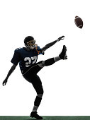 one caucasian american football player man kicker kicking in silhouette studio on white background