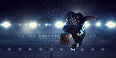 Confident American football player in lights of sport arena. Mixed media