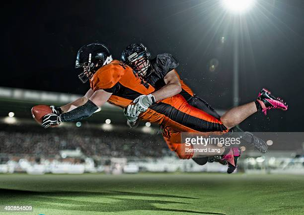 American football player tackling opponent