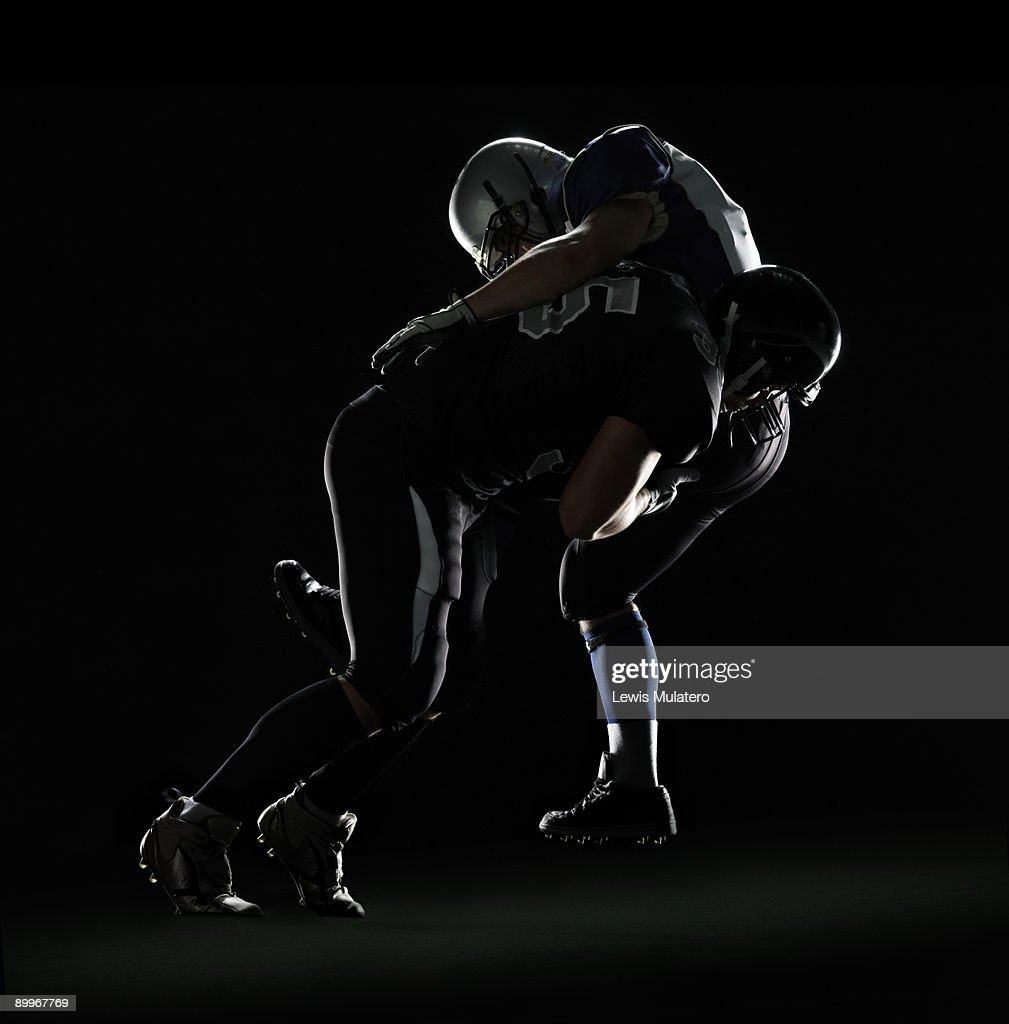American football player tackling opponent : Stock Photo