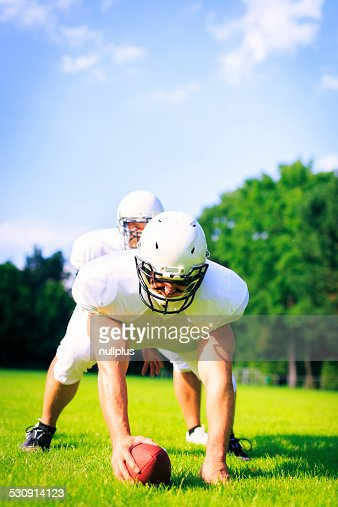 american football players at line of scrimmage