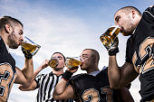American football players drinking beer against the sky.