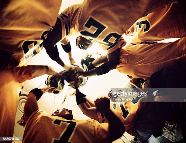 American football players in circle, cheering, upward view