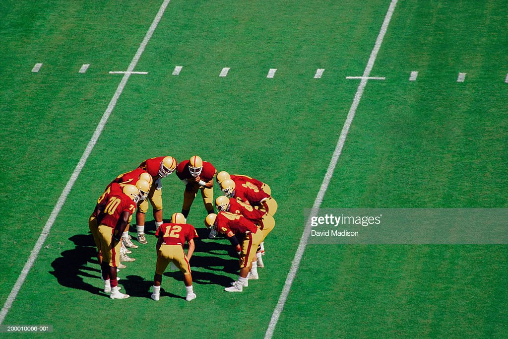 American football players standing in huddle on field, high angle view : Stock Photo