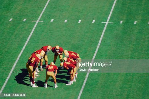 American football players standing in huddle on field, high angle view : Stockfoto