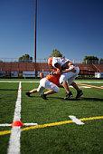 American football players (15-17) wrestling in field