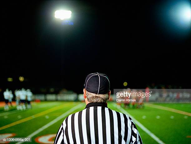 American football referee on field, rear view