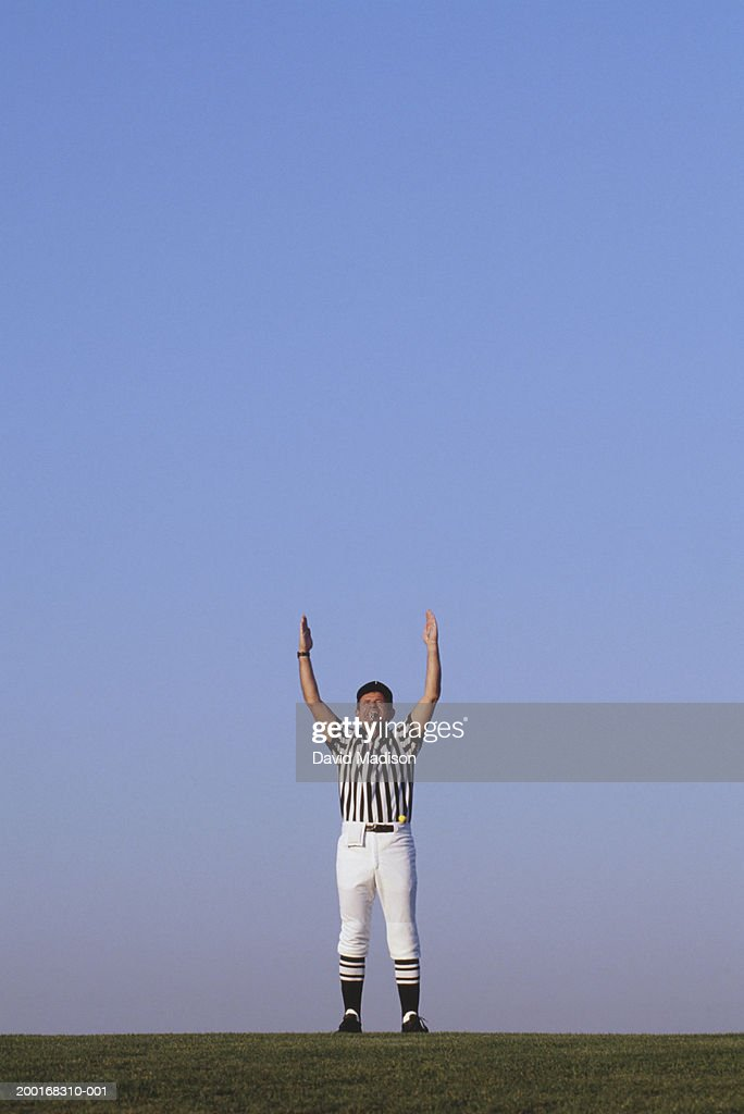 American football referee with both arms raised : Stock Photo