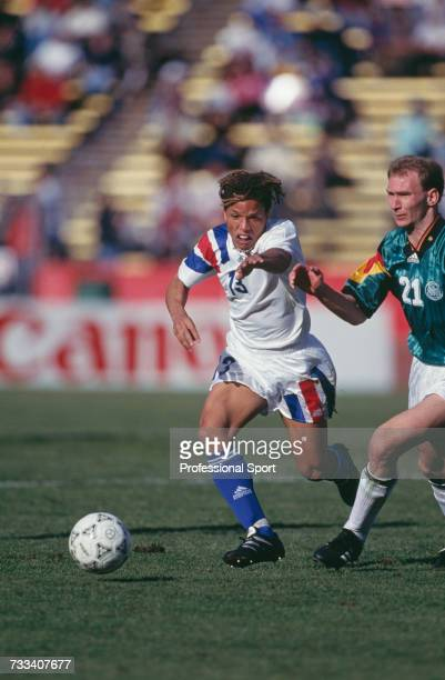 American footballer Cobi Jones clashes with German player Dieter Eilts as they both run for the ball during the international friendly match between...