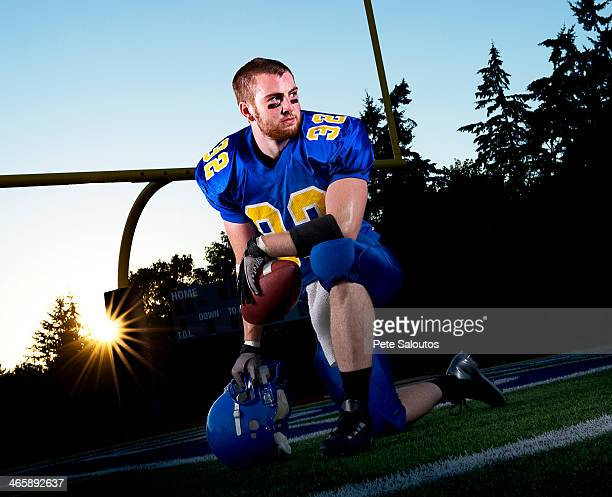 American footballer kneeling on pitch