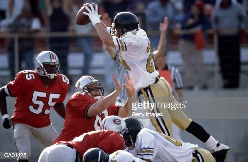 American Footballer leaping over opponents defense : Stock Photo