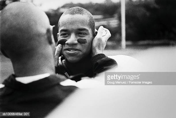 American footballer painting team-mates face, outdoors (B&W)
