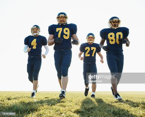 American footballers running on field against clear sky