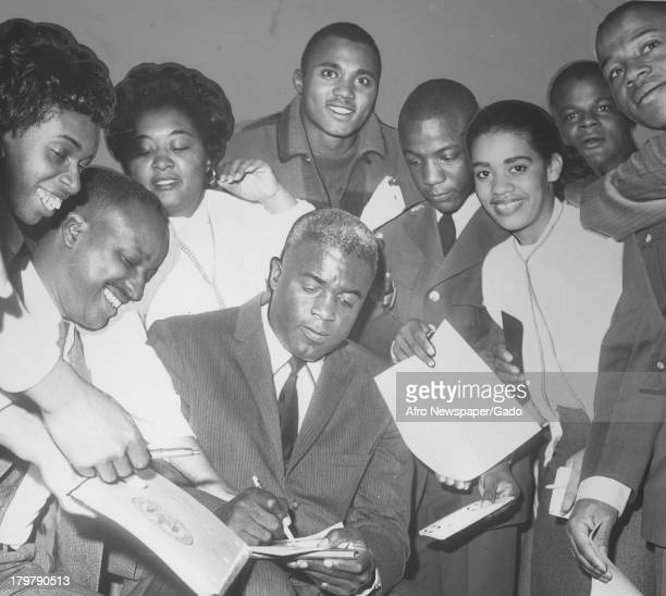 American former baseball player Jackie Robinson of the Brooklyn Dodgers is signing autographs October 29 1960