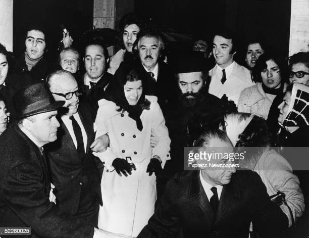 American former First Lady Jacqueline Kennedy Onassis wife of Greek shipping tycoon Aristotle Onassis is escorted through a crowd by her brotherinlaw...