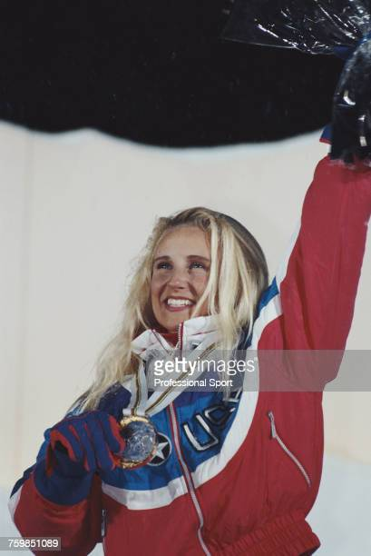 American freestyle skier Donna Weinbrecht waves one arm in the air in celebration on the medal podium after finishing in first place to win the gold...