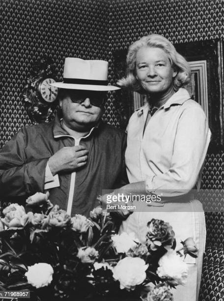 American friends writer Truman Capote and socialite CZ Guest pose together behind a vase of flowers 1976
