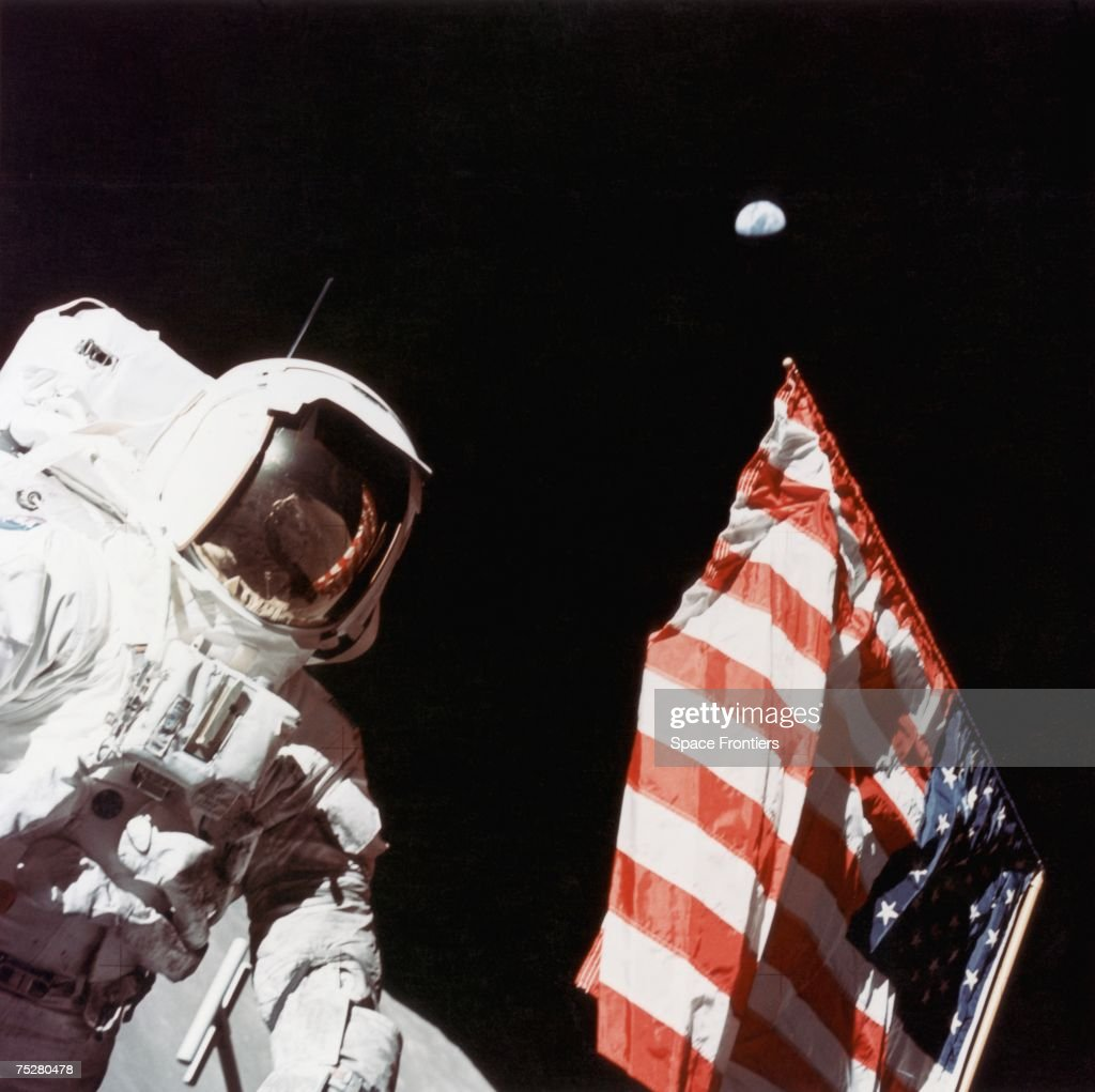 American geologist and Apollo 17 astronaut Harrison Hagan Schmitt stands next to the US flag on the surface of the moon, during a period of EVA (Extra-Vehicular Activity) at the Taurus-Littrow landing site, December 1972. The earth is visible in the far distance.