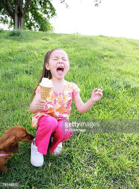 American girl eating soft ice cream with sitting beside dog