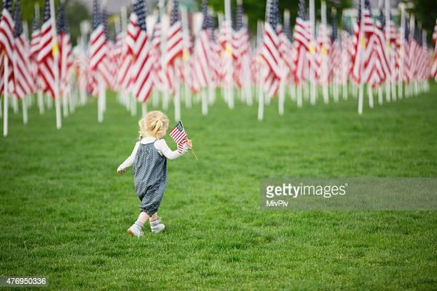 American girl walking in a field of flags