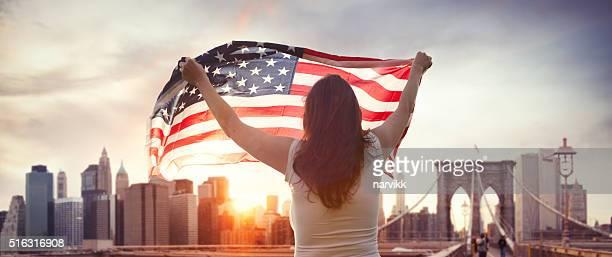 Américain jeune fille avec nous, drapeau sur le pont de Brooklyn à New York