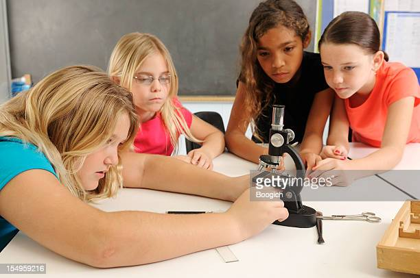 American Girls in Science Class with Microscope