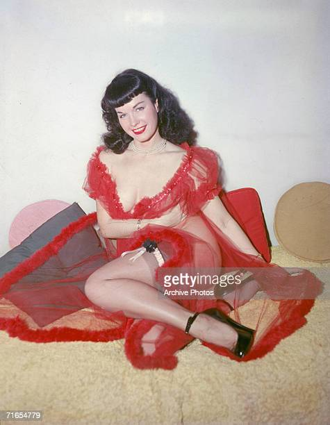American glamour model and pinup girl Bettie Page poses in a red negligee and stockings circa 1955