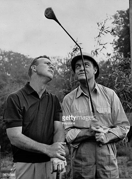 American golfer Arnold Palmer and entertainer Bob Hope examine a bent golf club during the filming of 'Call Me Bwana' at Denham west London