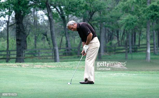 American golfer Arnold Palmer lines a shot at a golf tournament August 1982