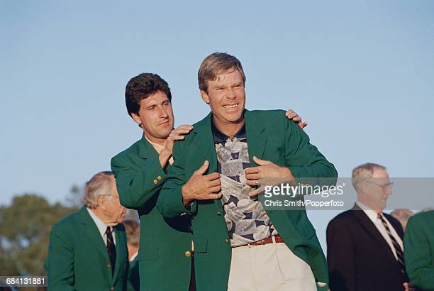 American golfer Ben Crenshaw is presented with his green jacket by the previous year's winner Spanish golfer Jose Maria Olazabal at the green jacket...