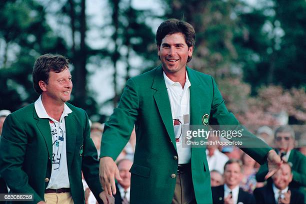 American golfer Fred Couples is presented with his green jacket by the previous year's winner Welsh golfer Ian Woosnam at the green jacket...