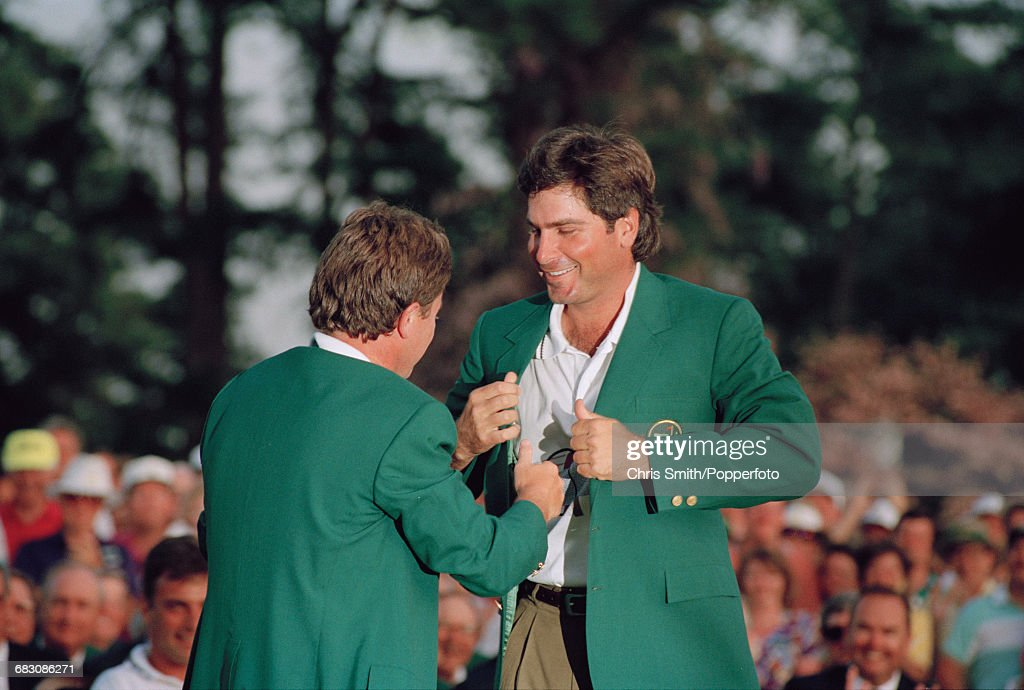 American golfer Fred Couples (right) is presented with his green jacket by the previous year's winner, Welsh golfer Ian Woosnam at the green jacket presentation ceremony after finishing in first place by two strokes to win the 1992 Masters Tournament at Augusta National Golf Club in Augusta, Georgia on 12th April 1992.