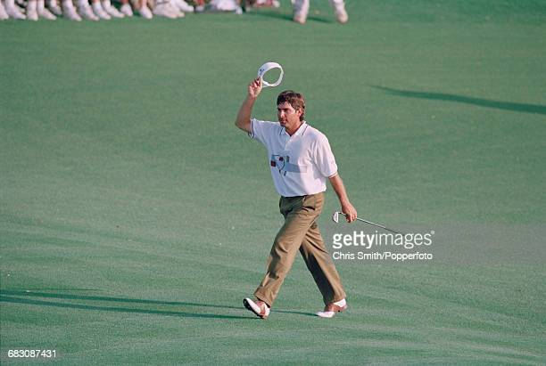 American golfer Fred Couples pictured raising his sun visor in the air on the 18th green during competition in the final round to finish in first...