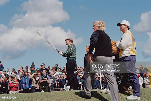American golfer Tom Watson pictured centre in action driving off from a tee watched by Australian golfer Greg Norman during play at the 1995 Open...