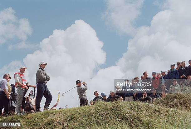 American golfer Tom Watson pictured in action driving off from a tee as fellow American golfer Steve Stricker watches on left during competition in...