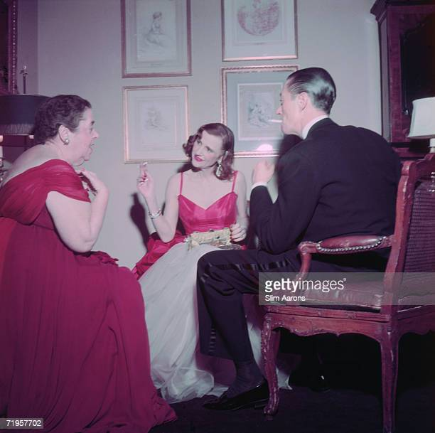 American gossip columnist and society hostess Elsa Maxwell and American songwriter Cole Porter with a friend at a New Year's Eve party given by...