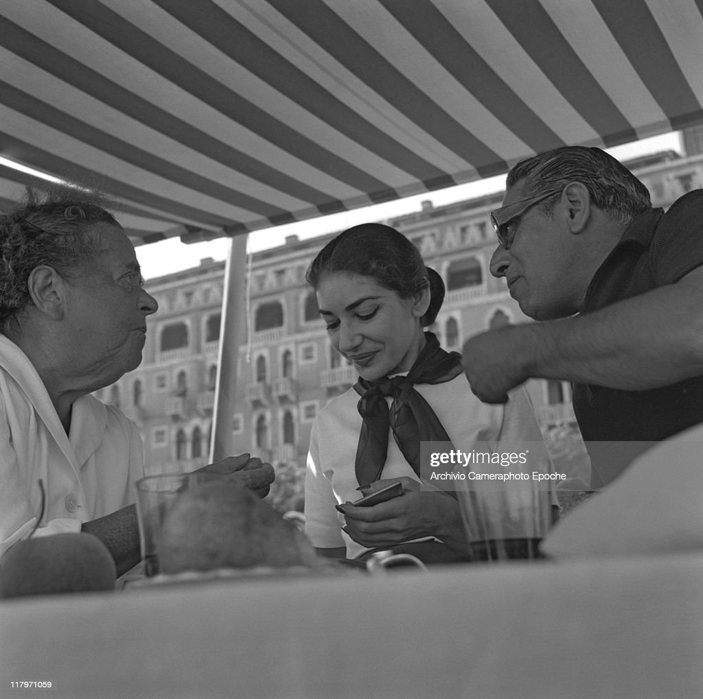 American gossip columnist Elsa Maxwell sitting at a table under a striped marquee with Maria Callas Meneghini and Aristotele Onassis at their first...
