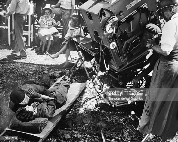 American Gregory Peck and Ava Gardner lie on a strecher and embraceas they are filmed by the crew in a scene from 'The Snows of Kilamanjaro' 1952 The...